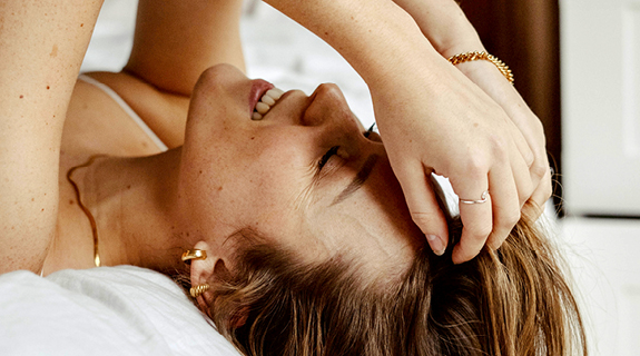 Frau liegt auf Bett