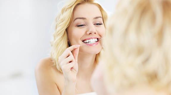 Frau reinigt ihre Zähne